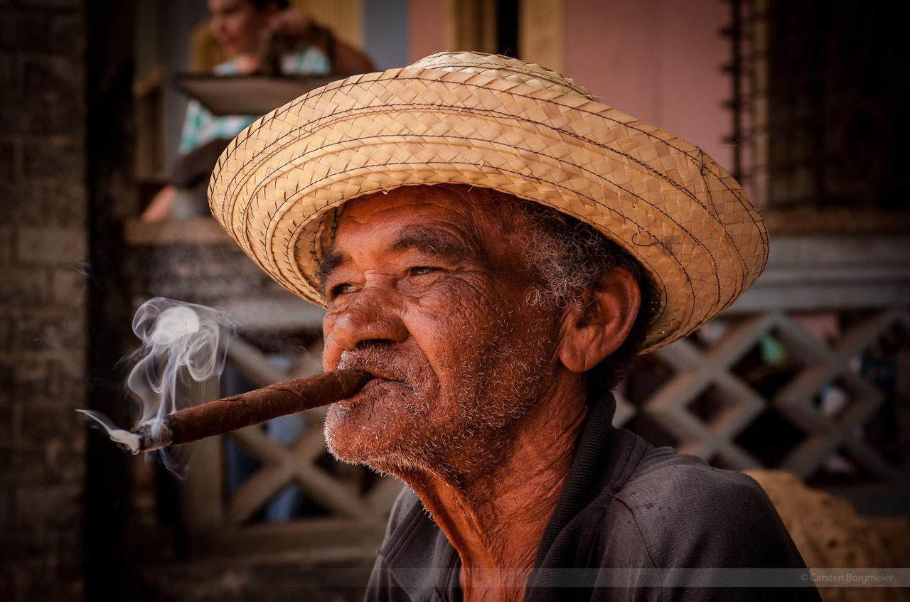 Alter Mann raucht in Vinales genüsslich eine Zigarre.